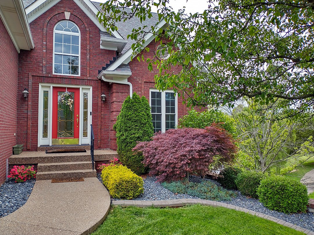 Exterior of red brick home with landscaping. Includes a red japanese maple, arbor vitae, boxwoods, flowering Bradford Pear tree, and blue stone
