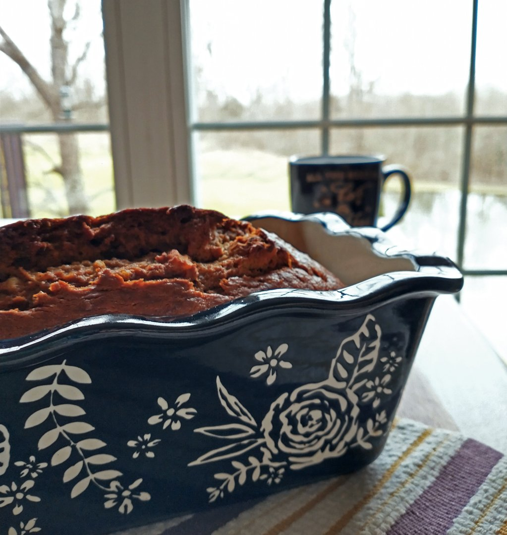 banana bread in ceramic pan with coffee mug on a cloudy morning