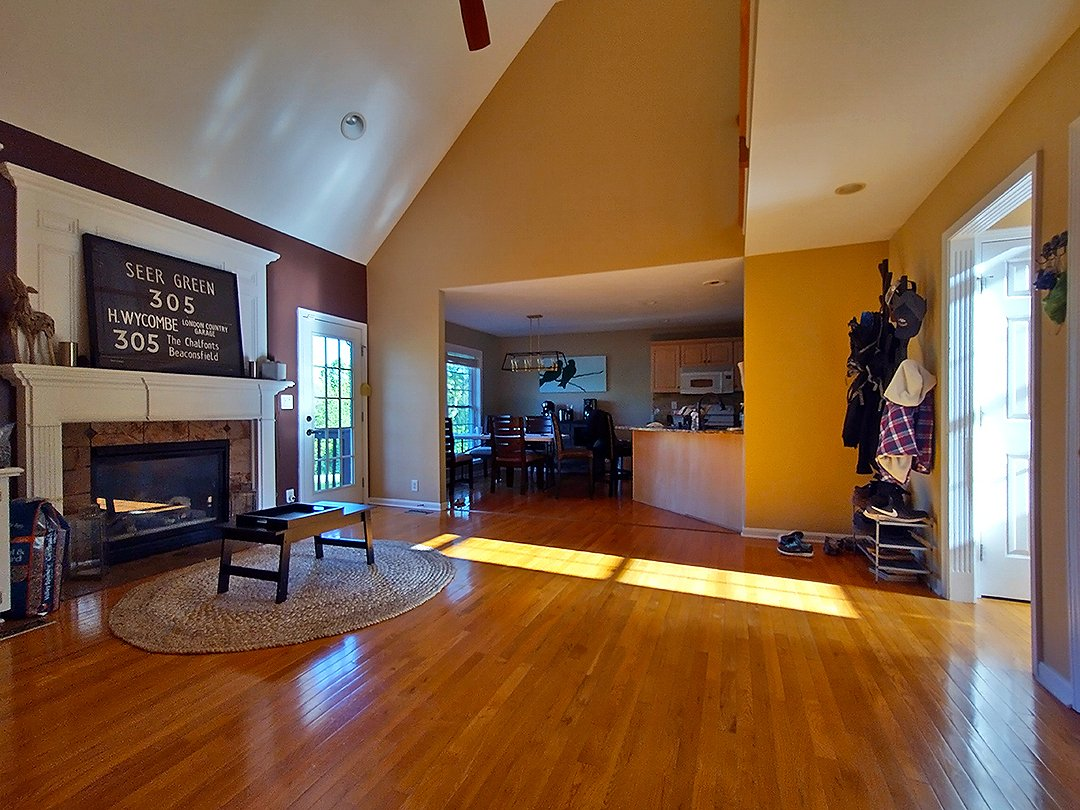 living room wide angle view with the kitchen and vaulted ceiling